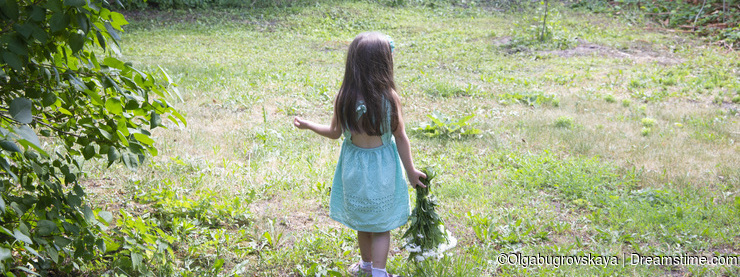 Little girl portrait back to camera with with a bouquet of daisies