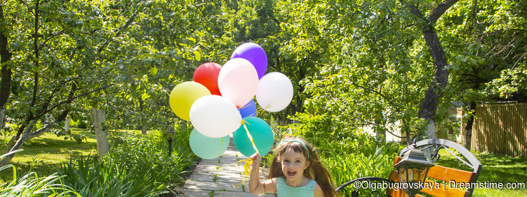 Little girl with colored balloons running down the path in the garden