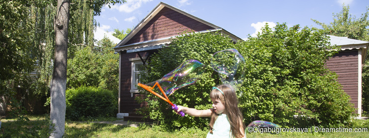 Little girl blows bubbles in the garden