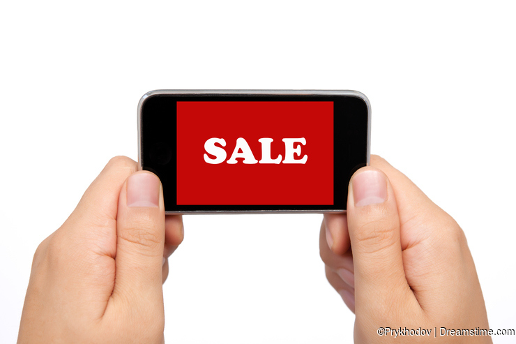 Female hands holding a phone with sale