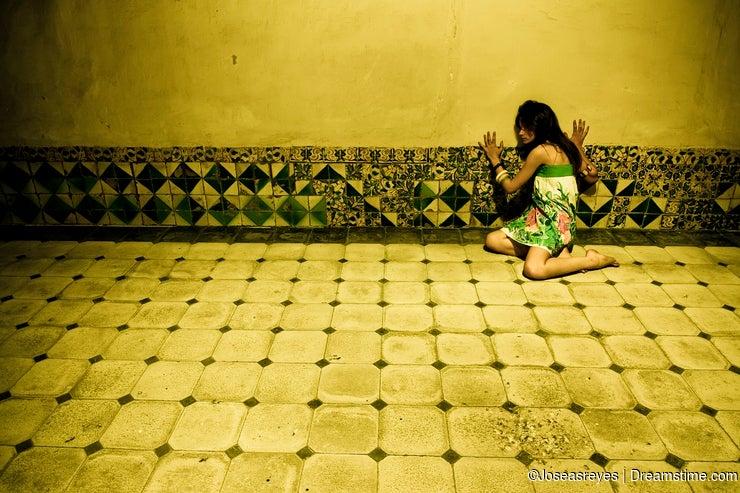 Terrified woman on wall