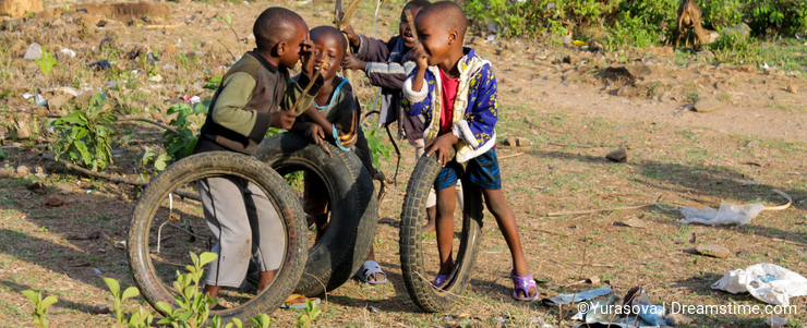 African poor boys play with a wheel