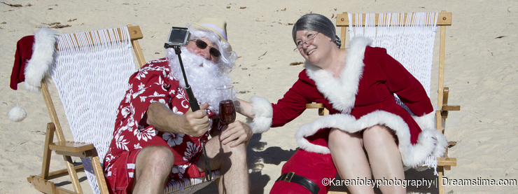 Santa and Mrs Claus taking selfie on beach