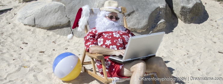 Santa Claus working on beach chair working with laptop computer