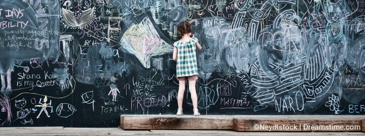 Little girl writing on big blackboard