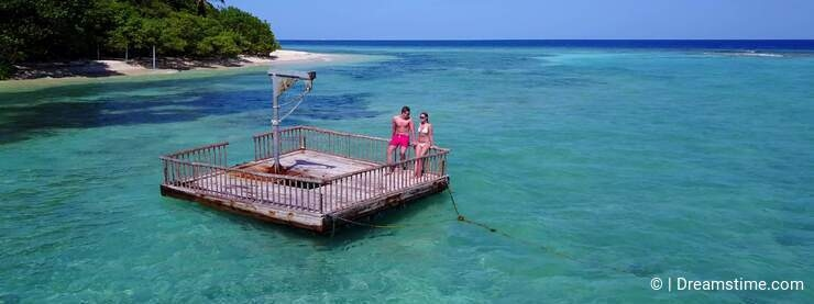 V08551 2 young people couple romantic sunbathing on pontoon with aerial view in beautiful clear aqua blue sea water