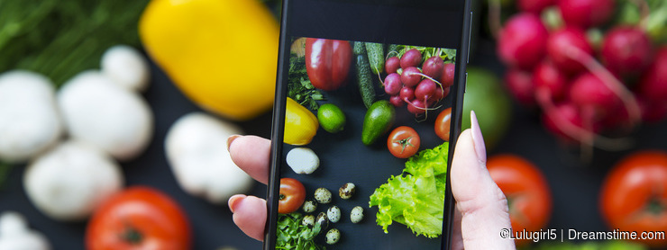 Girl taking picture of healthy food with her smartphone. Vegan f