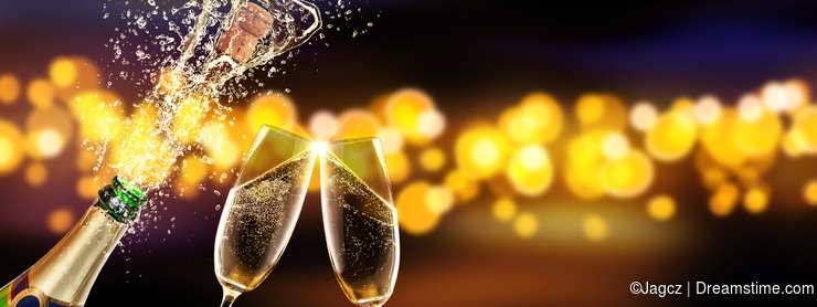Bottle of champagne with glass over blur background