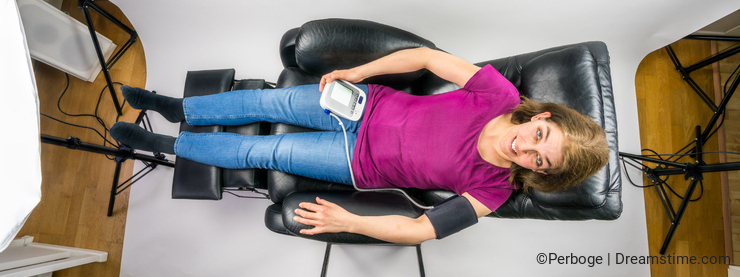 Above view of mature woman lying down in recliner chair holding a blood pressure machine. Behind the scene photo session