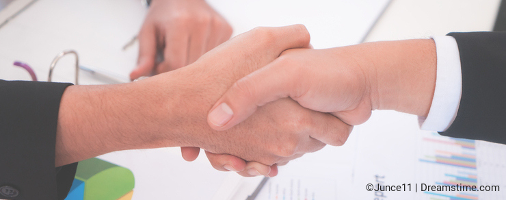 Business hand shake with Chart sheet on meeting table