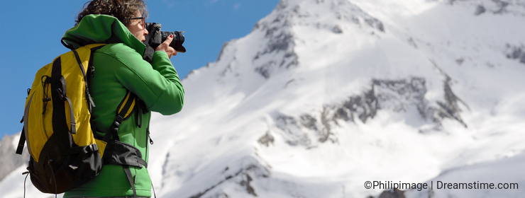 Hiker with camera and backpack taking picture of beautiful mount