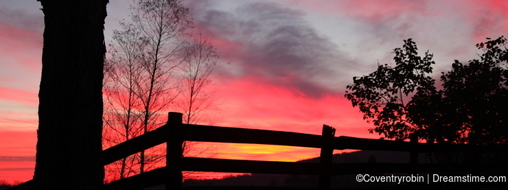 Shades of color at sunset over a rural fence