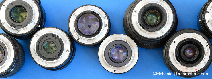 Several photographic lenses lie on a bright blue background. Spa
