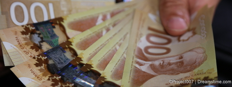 A close up of a man's hand holding Canadian money