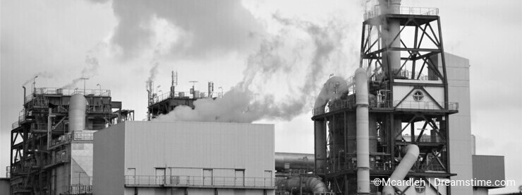 Industrial plant spews clouds into gray sky