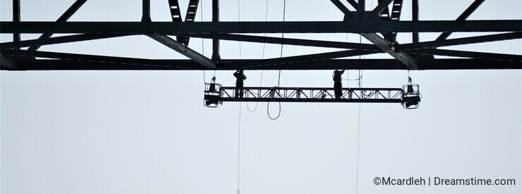 Two bridge workers silhouetted under deck slab