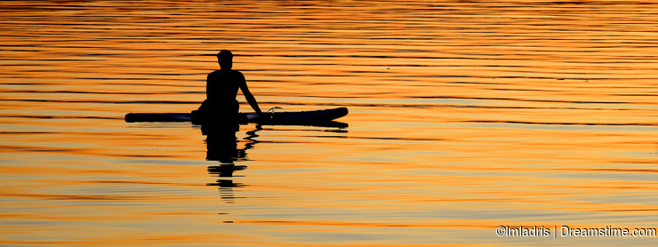 Silhouetted paddle boarder peaceful sunset