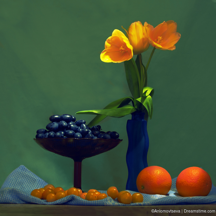 Still life yellow tulips, tomatoes, black grapes and two oranges on a green background