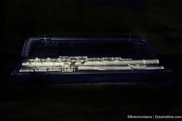 Silver disassembled flute in an open case on a black background