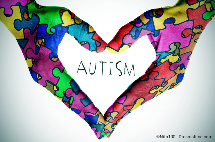 Text autism and hands forming a heart with puzzle pieces