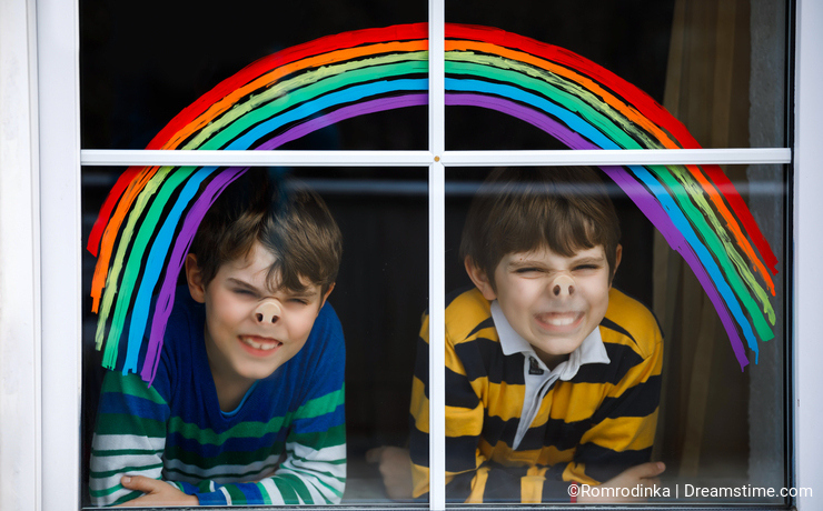 Two kids, school boys, siblings and best friends with rainbow painted with colorful window color during pandemic