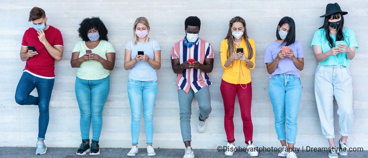 Young people wearing face safety masks using smart mobile phones while keeping social distance during coronavirus time -