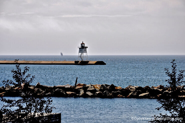 A Sailboat passes by the Lighthouse in Grand Marais, Minnesota