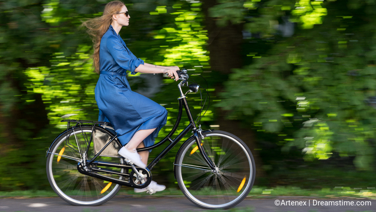 Beautiful young woman and vintage bicycle, summer. Red hair girl riding the old black retro bike outside in the park.