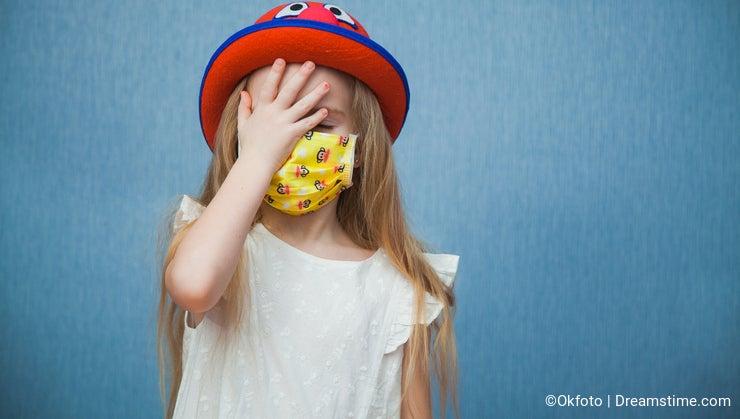 Portrait of scared child on quarantine wearing medical mask on pandemic.