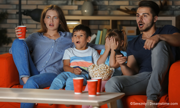 Family watching TV on sofa in evening