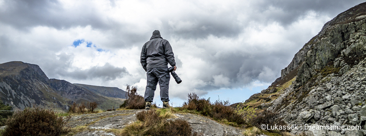 Photographer standing on mountain observing the dramatic sky