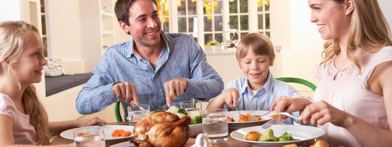 Stock photo: happy family having roast chicken dinner at table