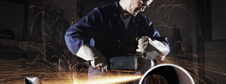 Stock photo: worker cutting pipe with angle grinder.