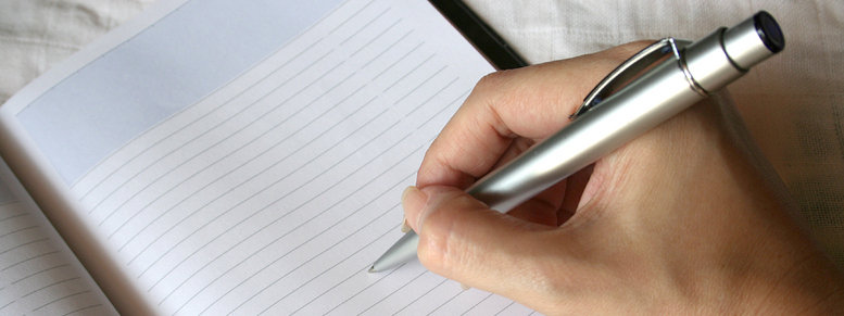 Stock photo: hand holding pen writing on note book