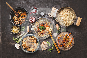 Asian food cooking. Wok with noodles chicken stir fry and vegetables ingredients with spices ,sauces and chopsticks on dark rustic