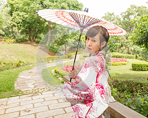 Asian woman wearing a yukata and holding an umbrella in Japanese