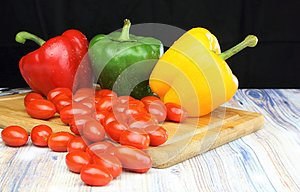 Bell peppers and baby tomatoes on a chopping board black background