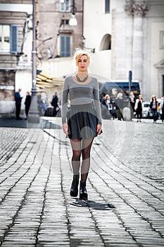 Blonde girl walking on the street in the city wearing a skirt.