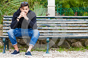Boyfriend waiting. Handsome young man model sitting on the bench