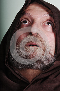 Capuchin monk with a beard illuminated by faith praying god