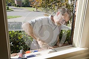 Carpenter repairing window frame