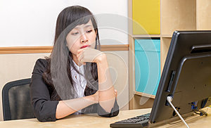 Chinese businesswoman at desk looking at monitor