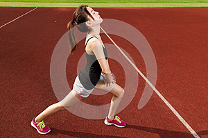 Chinese female athlete stretching legs on sports f