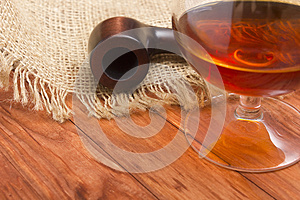 Cognac and tobacco pipe on a wooden table