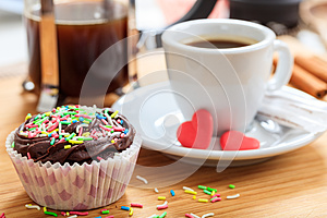 Cup of coffee and a cup cake on a wooden surface