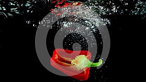 Cut off half of red sweet pepper falls into water super slow motion shot