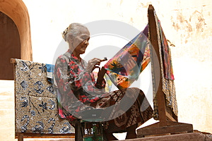 Elderly woman making traditional batik