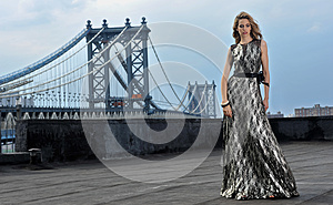 Fashion model posing sexy, wearing long evening dress on rooftop location
