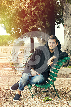 Fashionable cool young man relaxing on a bench in a park with trees
