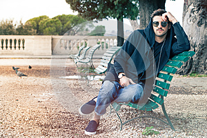 Fashionable cool young man with sunglasses relaxing on a bench